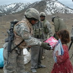 Sgt. Bobbie Pettway, 27th Engineer Battalion, offers school supplies to a young Afghan girl